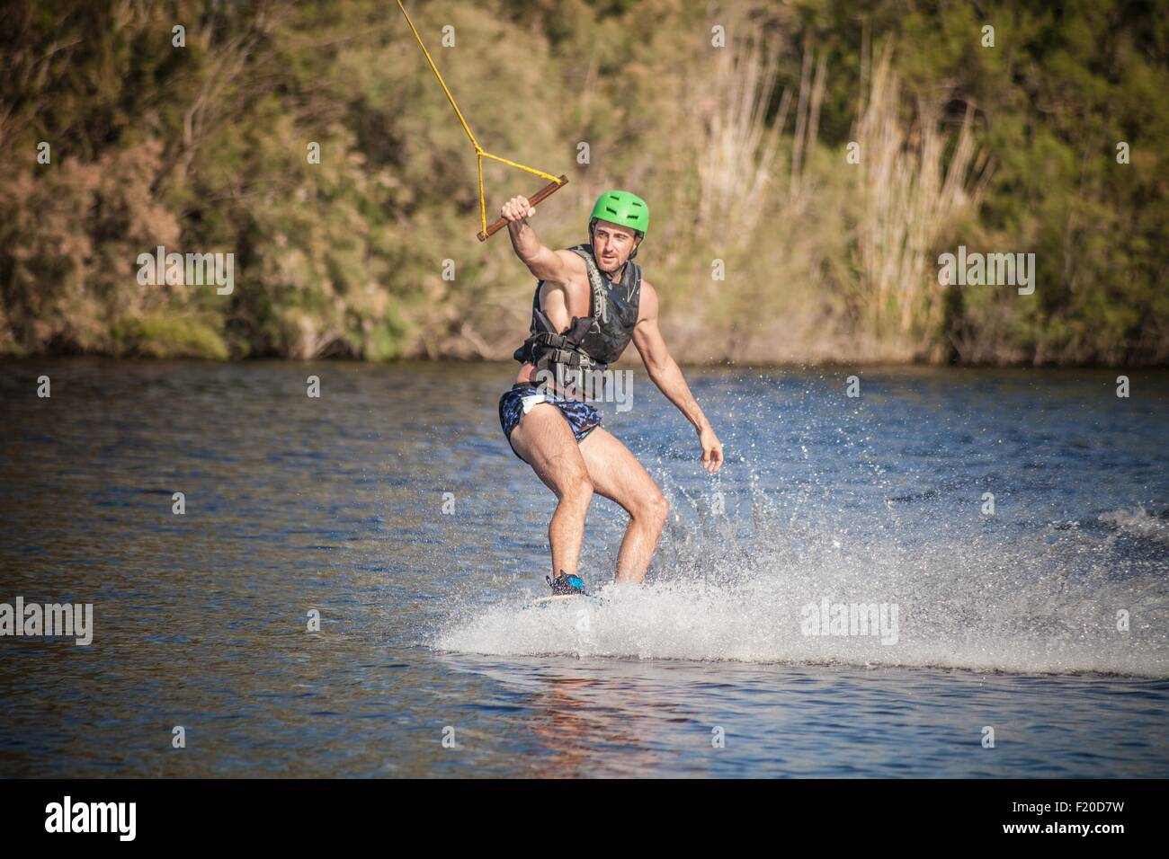 Young man in sea wakeboarding, Cagliari, Sardinia, Italy - Stock Image