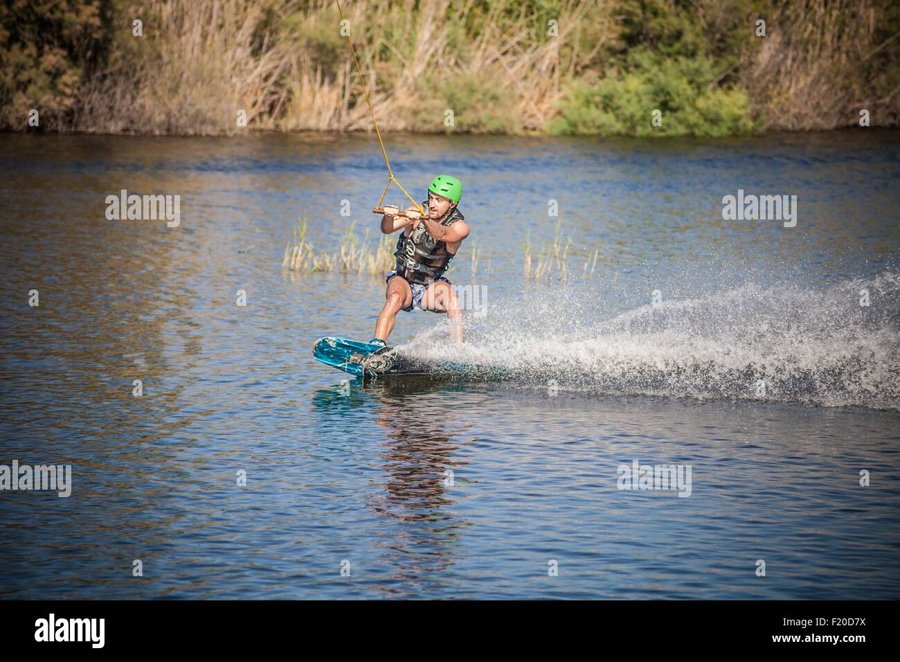 Young man wakeboarding in sea, Cagliari, Sardinia, Italy - Stock Image