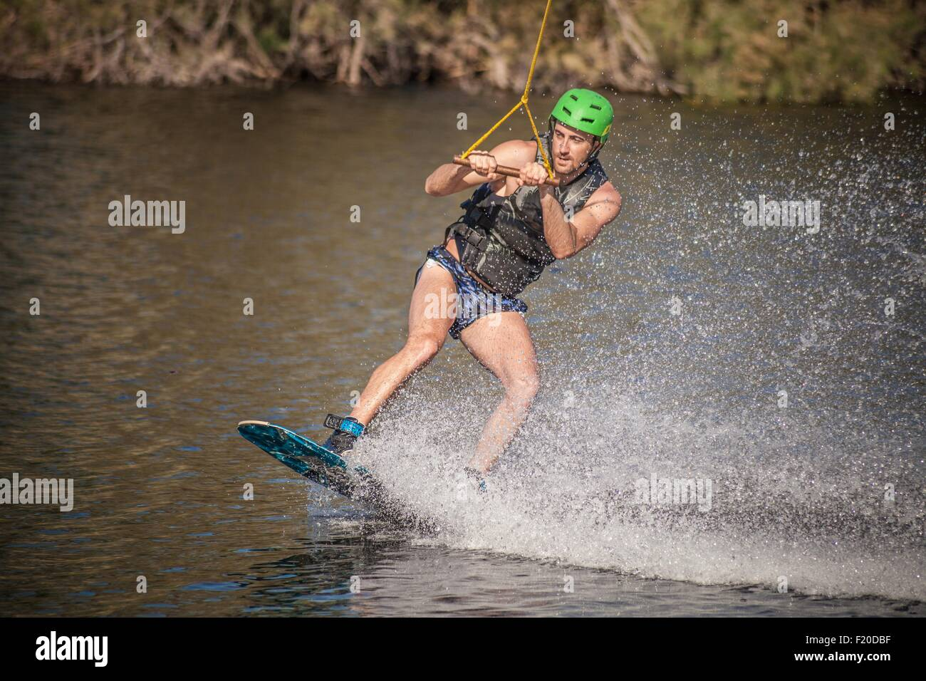Young male wakeboarder swerving in sea, Cagliari, Sardinia, Italy - Stock Image