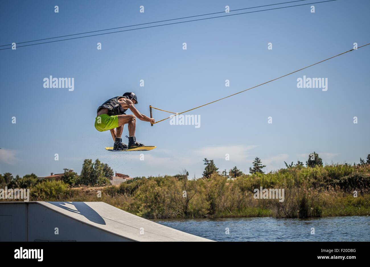 Mid adult male wakeboarder jumping ramp in sea, Cagliari, Sardinia, Italy - Stock Image