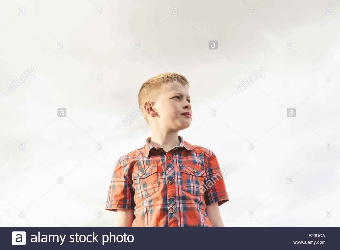 Portrait of boy looking away against overcast sky - Stock Image