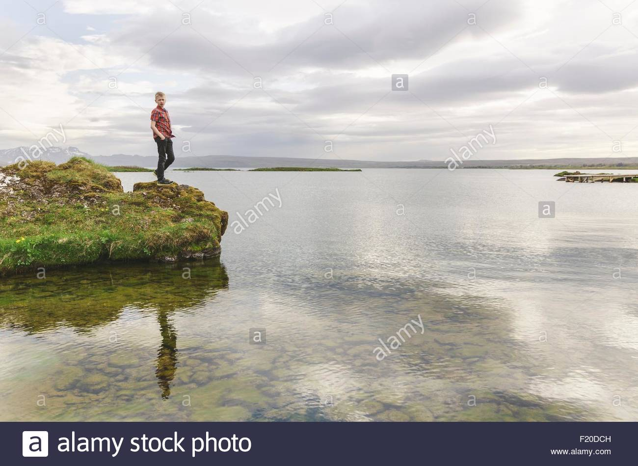 Boy looking down from lakeside, Thingvellir, Iceland - Stock Image