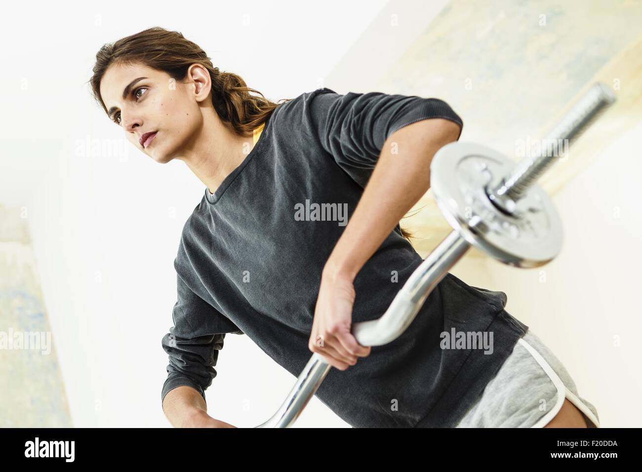 Angled view of young woman lifting barbell in living room - Stock Image