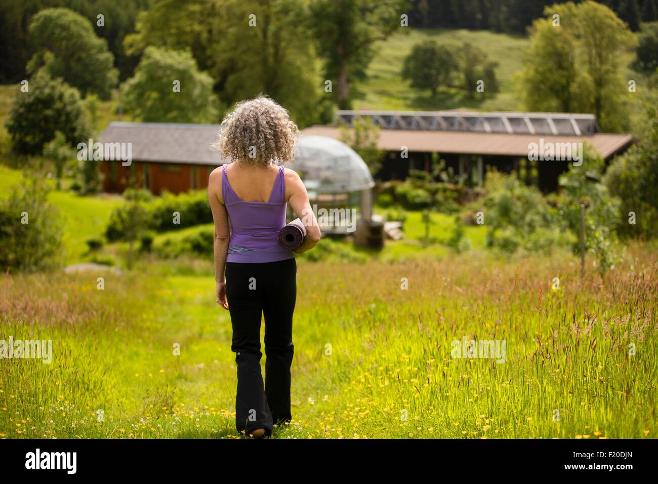 Rear view of mature woman carrying yoga mat walking in eco lodge field - Stock Image