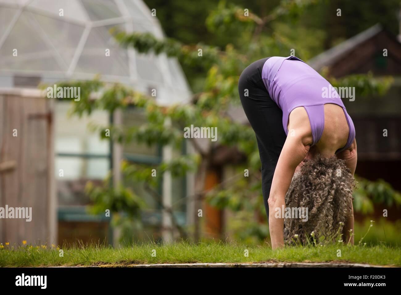 Mature woman practicing yoga forward fold in eco lodge garden - Stock Image