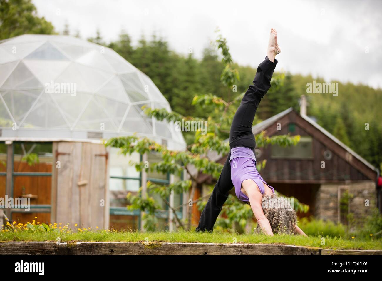 Mature woman practicing yoga with leg raised in eco lodge garden - Stock Image