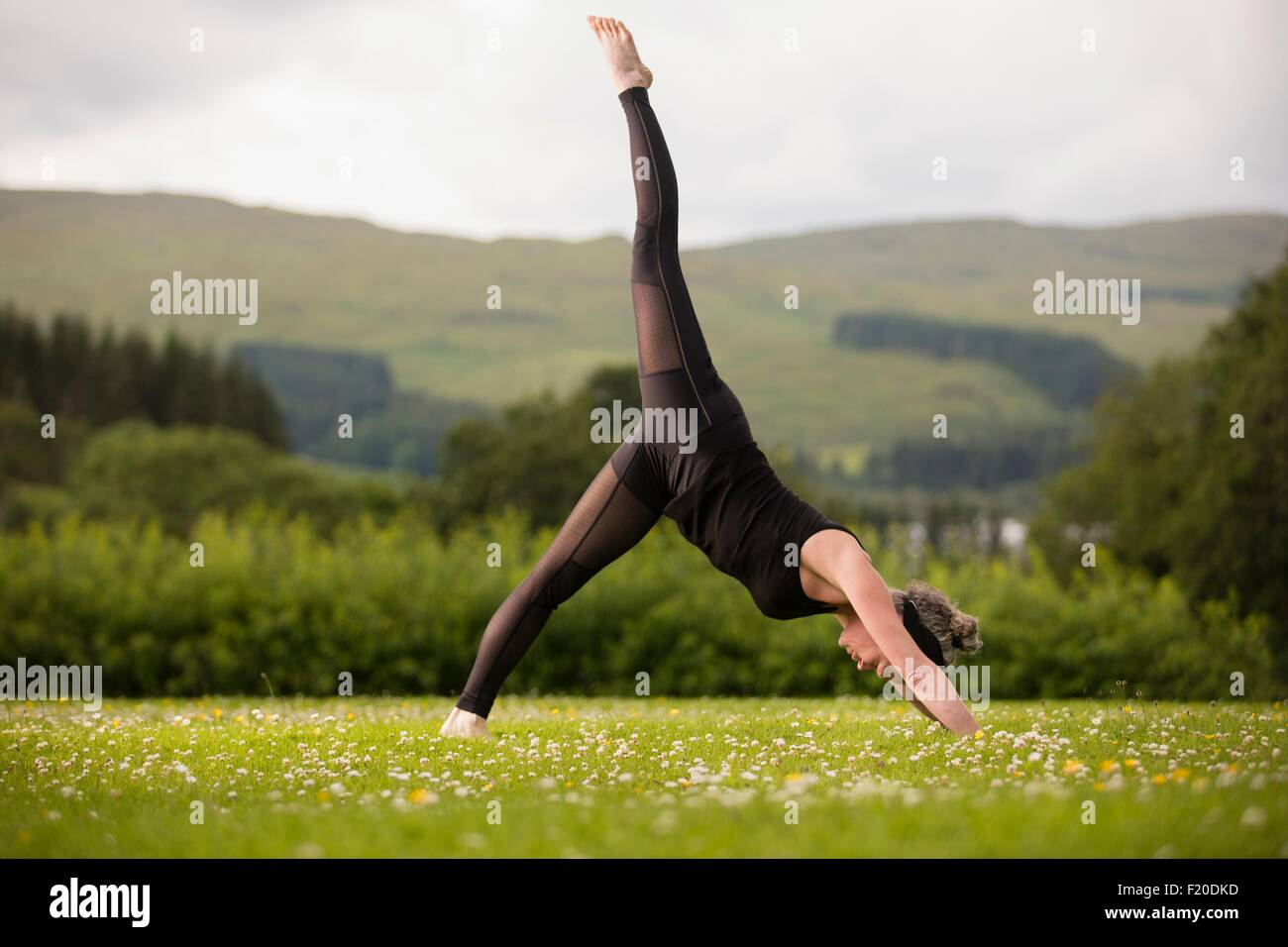 Mature woman practicing yoga leg lift in field - Stock Image