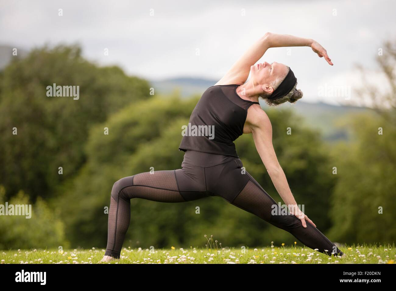 Mature woman practicing yoga pose in field - Stock Image