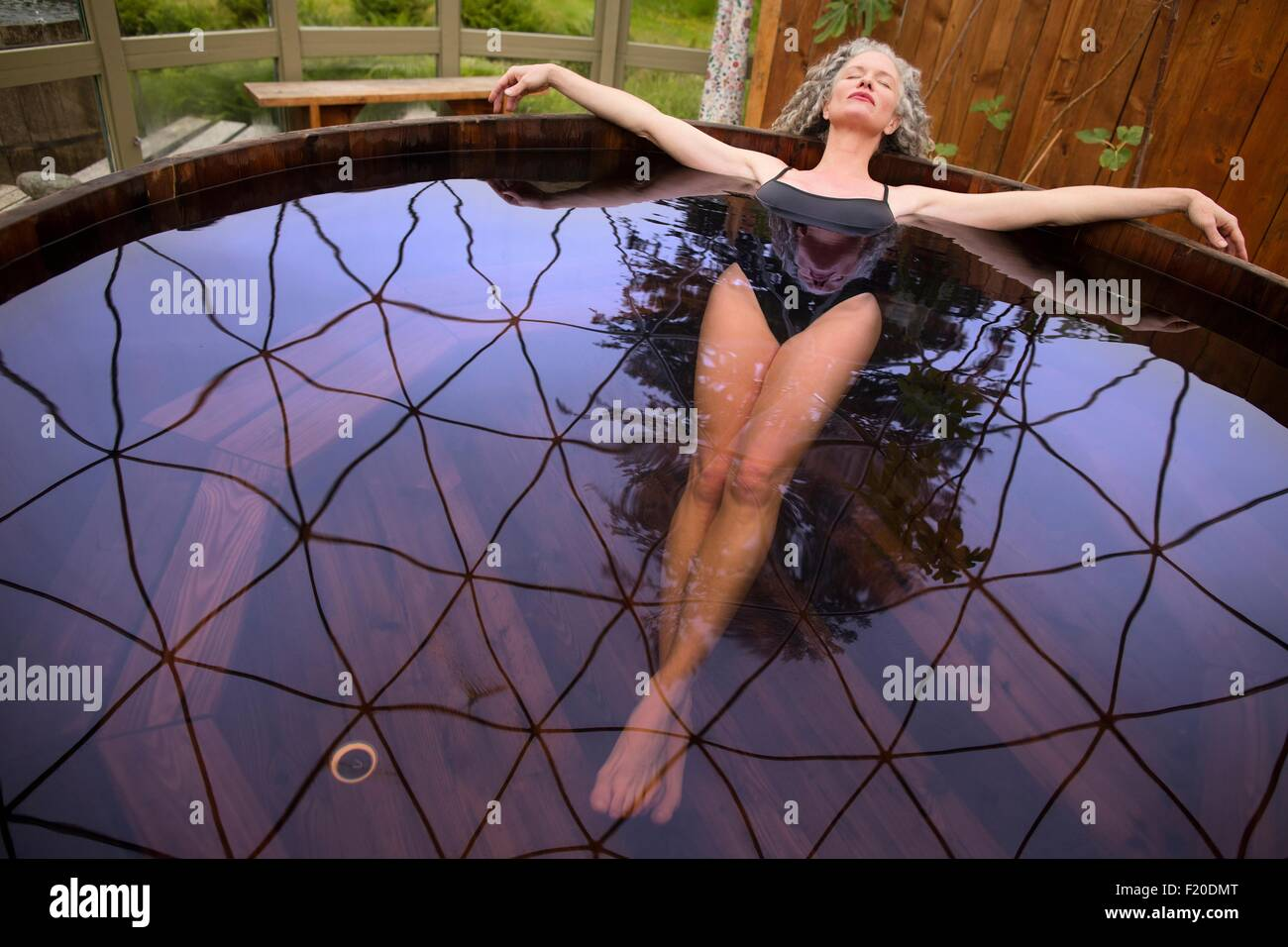 Mature woman lying back in hot tub at eco retreat - Stock Image