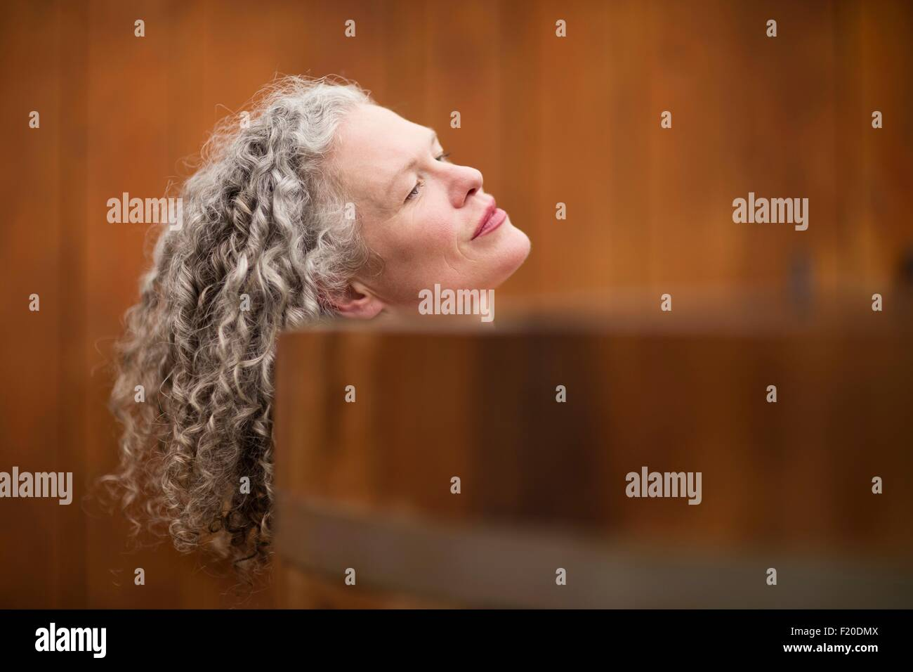 Mature woman resting on edge of hot tub at eco retreat - Stock Image