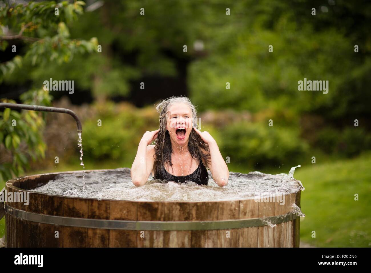 Mature woman in fresh cold water tub at eco retreat - Stock Image