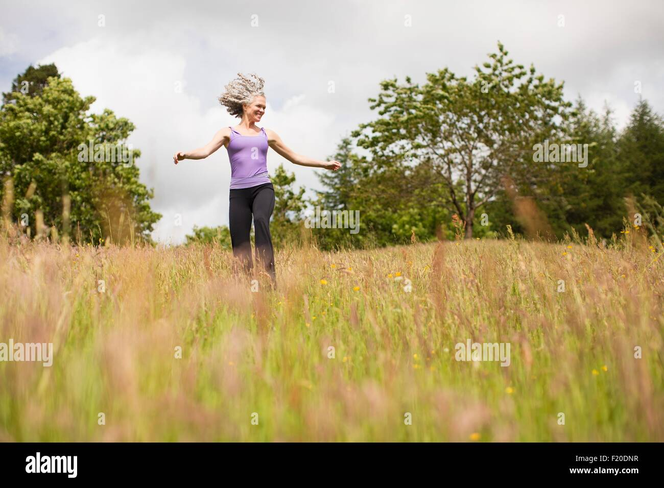 Mature woman with long grey hair running through field - Stock Image
