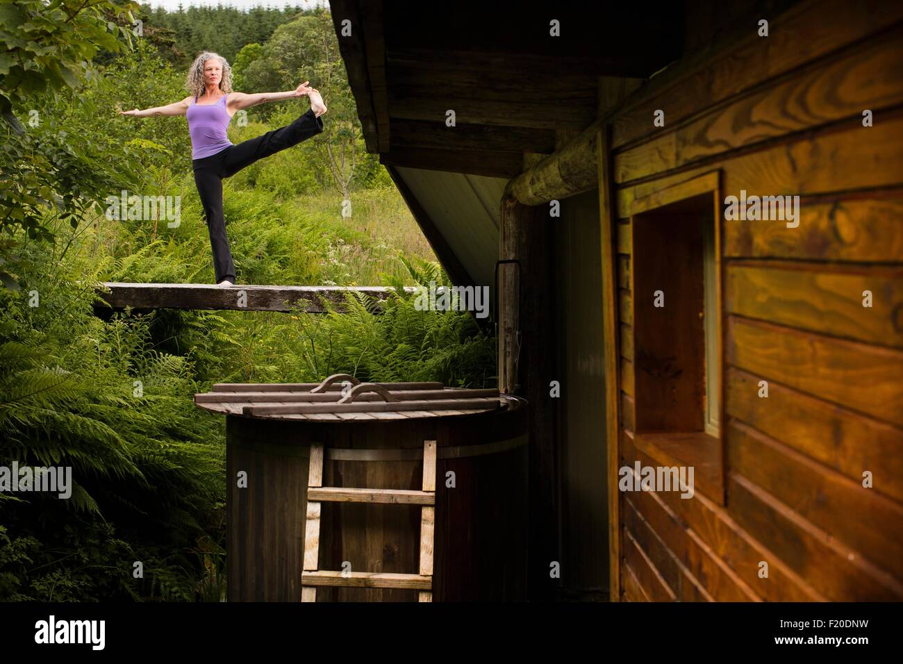 Mature woman practicing yoga pose on footbridge at eco lodge - Stock Image