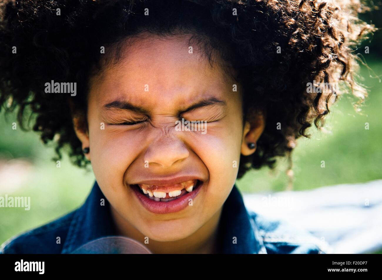 Close up portrait of girl with eyes closed pulling face - Stock Image