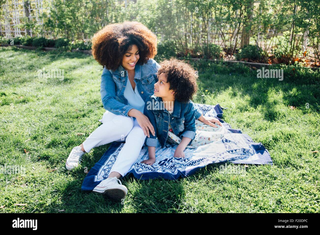 Mother with arm around daughter sitting on blanket - Stock Image