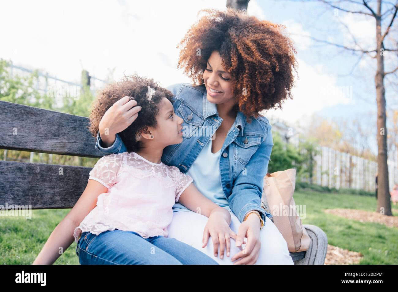 Mother with arm around daughter sitting on park bench face to face - Stock Image
