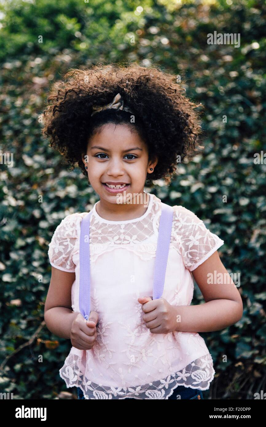 Waist up portrait of girl wearing backpack, looking at camera smiling - Stock Image