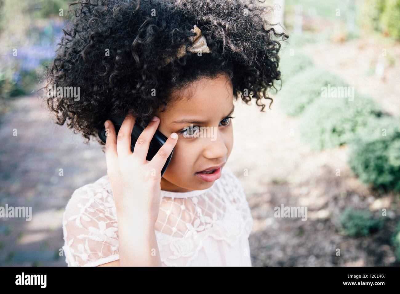 Head and shoulders of girl using smartphone to make a telephone call - Stock Image