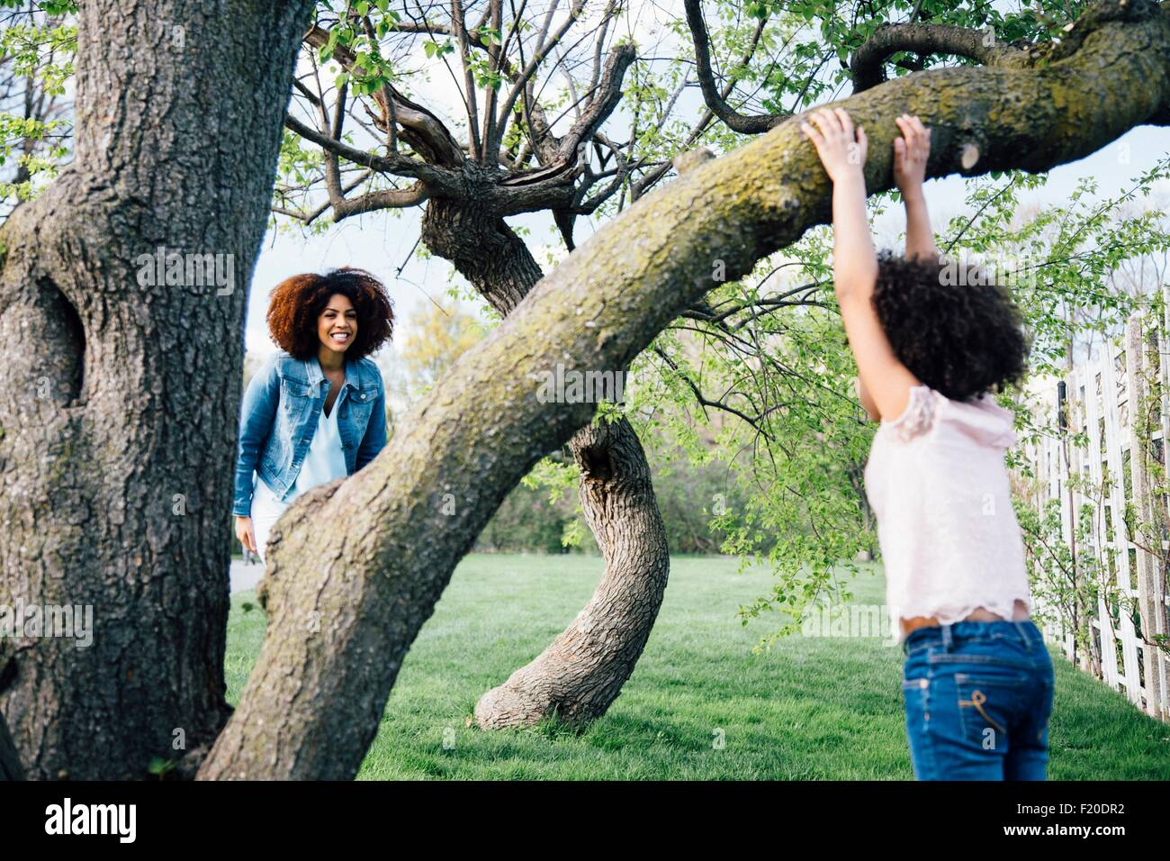 Mother smiling at daughter climbing tree - Stock Image
