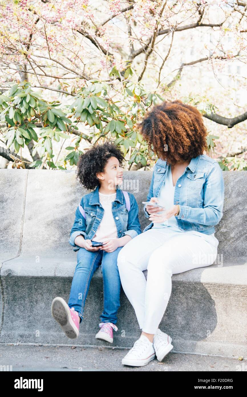 Mother and daughter sitting side by side holding smartphone's, face to face - Stock Image