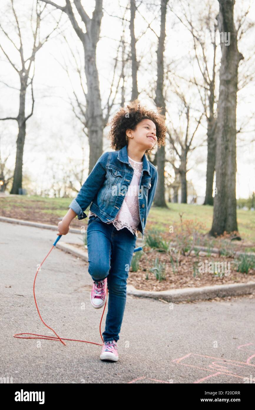 Girl standing on one leg, playing with skipping rope, looking up - Stock Image