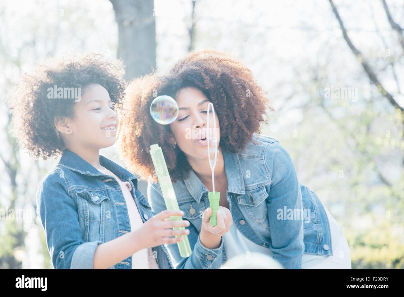 Mother and daughter blowing bubbles together Stock Photo