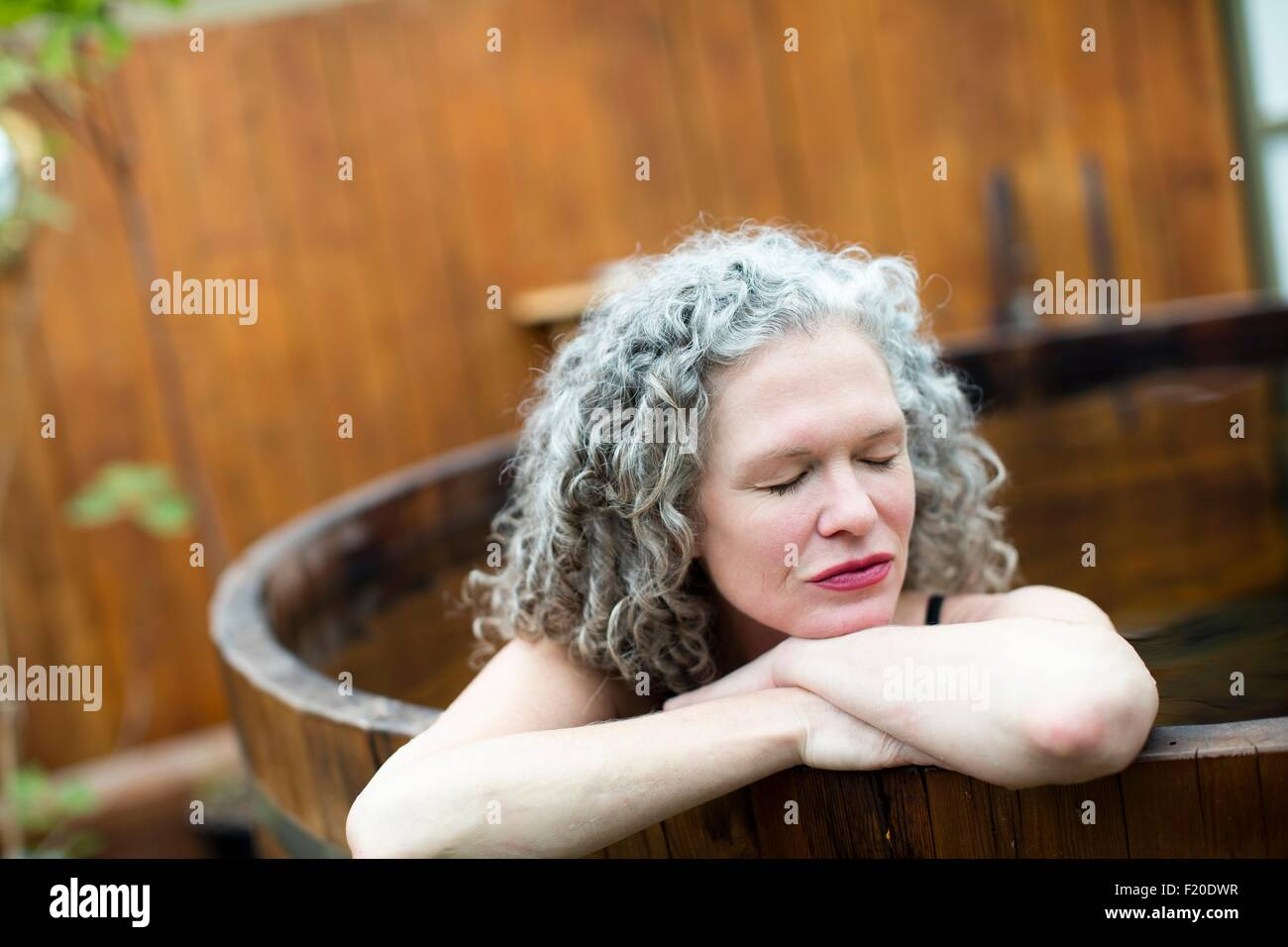 Mature woman resting on hands in hot tub at eco retreat - Stock Image