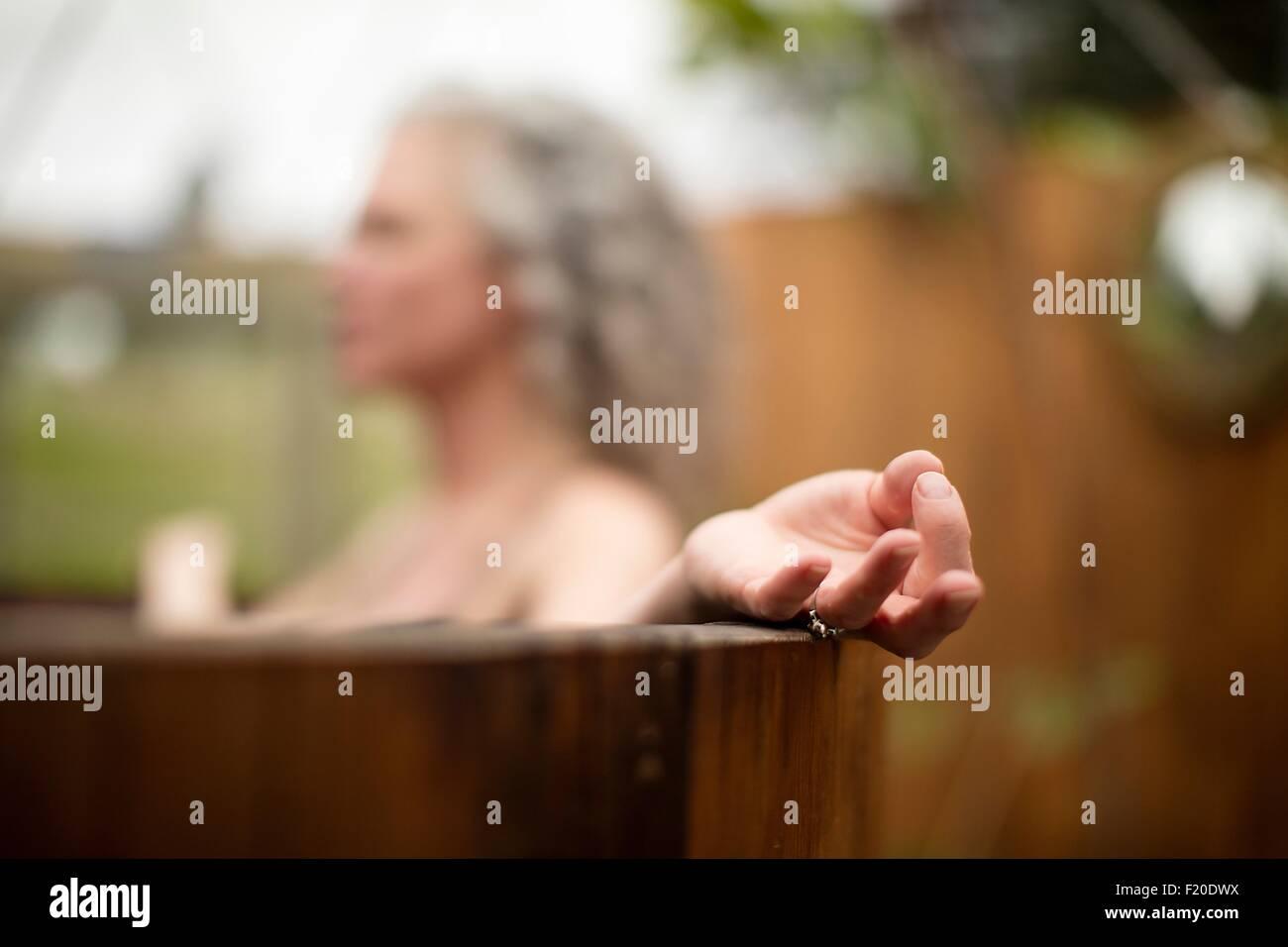 Mature woman meditating in hot tub at eco retreat - Stock Image