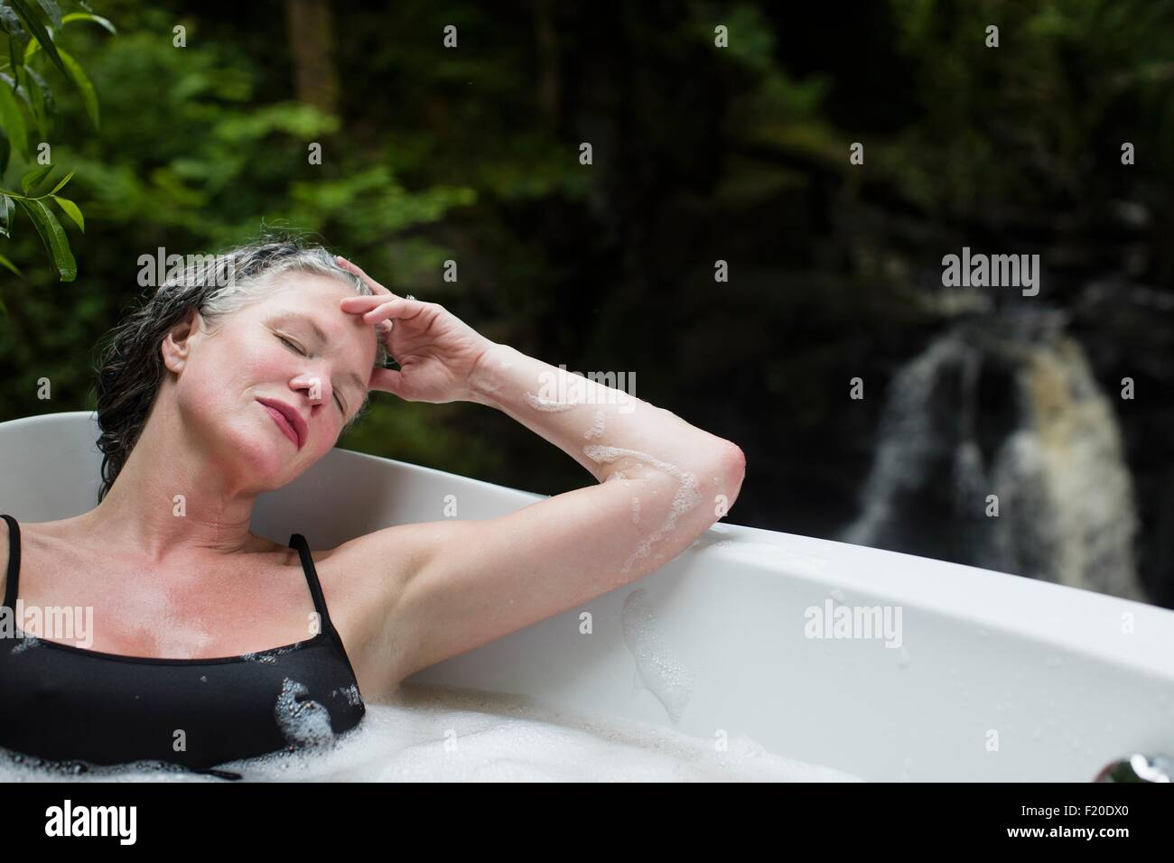 Mature woman with eyes closed in bubble bath in front of waterfall at eco retreat - Stock Image