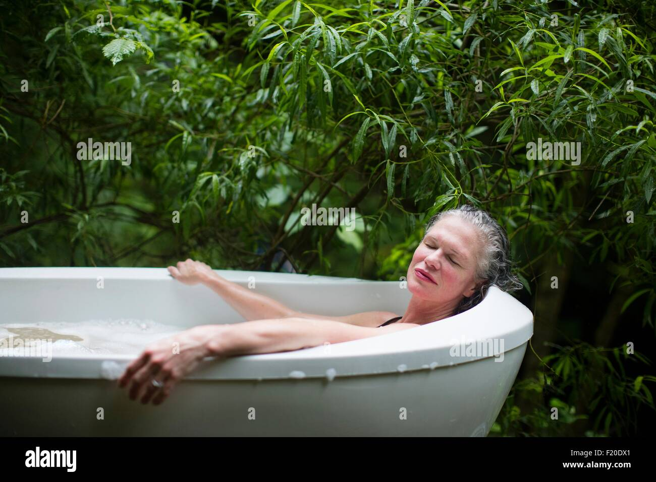 Mature woman relaxing in garden bubble bath at  eco retreat - Stock Image