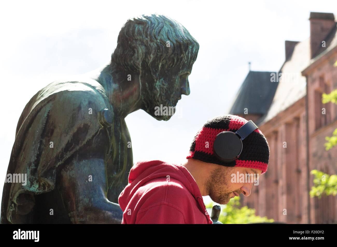 Head and shoulder portrait of mid adult man wearing headphones in front of sculpture, Freiburg, Baden, Germany - Stock Image