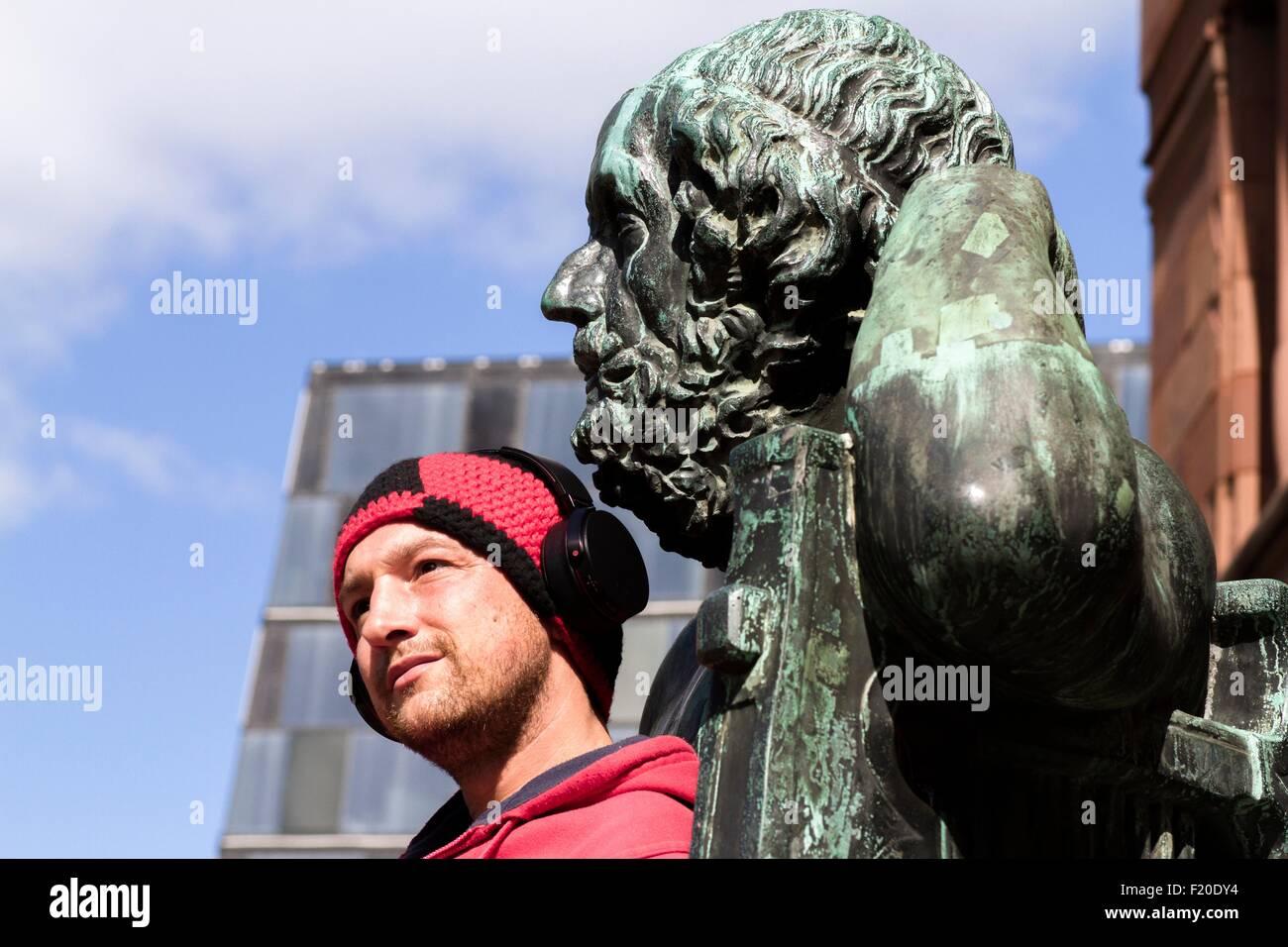Portrait of mid adult man wearing headphones in front of sculpture, Freiburg, Baden, Germany - Stock Image