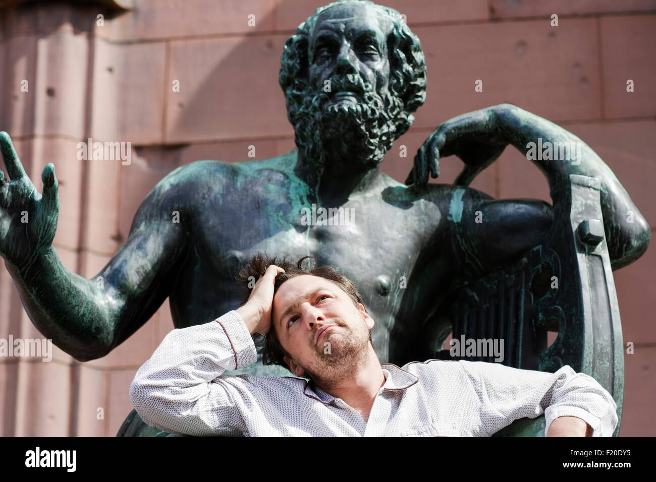 Portrait of mid adult man with hand in hair in front of sculpture, Freiburg, Baden, Germany - Stock Image