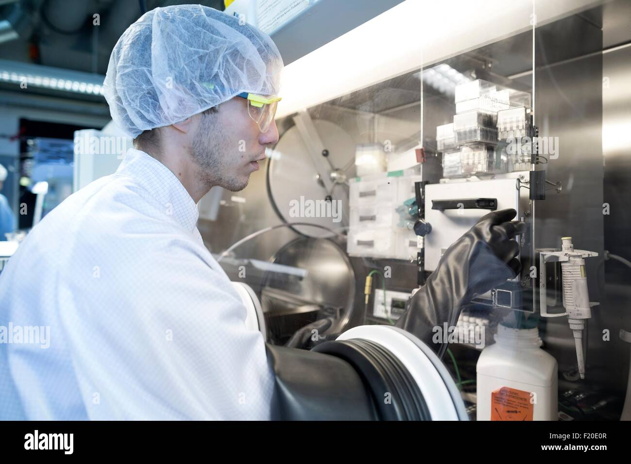Male scientist adjusting switch in fume hood in lab cleanroom - Stock Image