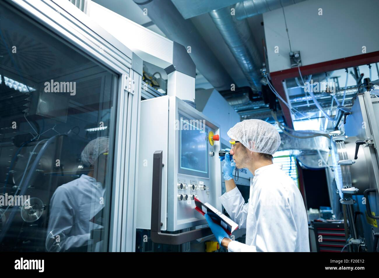 Male scientist with notebook adjusting control panel in lab cleanroom - Stock Image