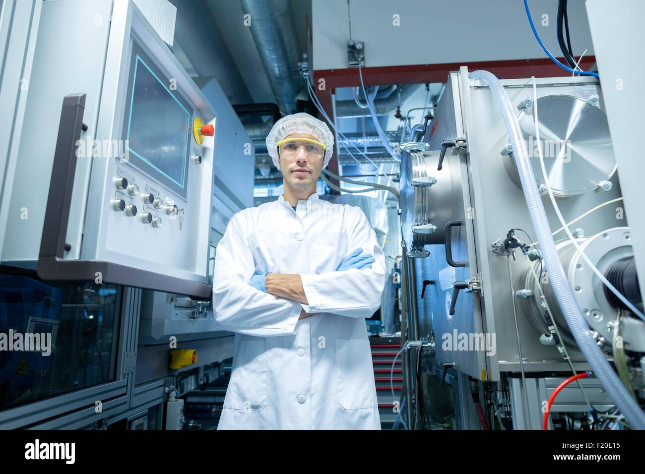 Portrait of male scientist with arms folded in lab cleanroom Stock Photo