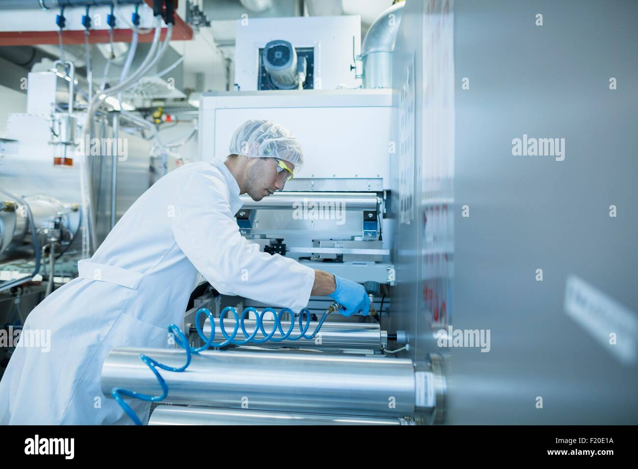 Male scientist power cable in lab cleanroom - Stock Image