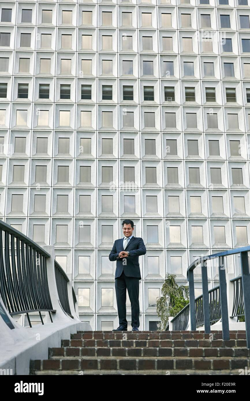 Low angle view of business man standing at top of stairway looking at watch - Stock Image