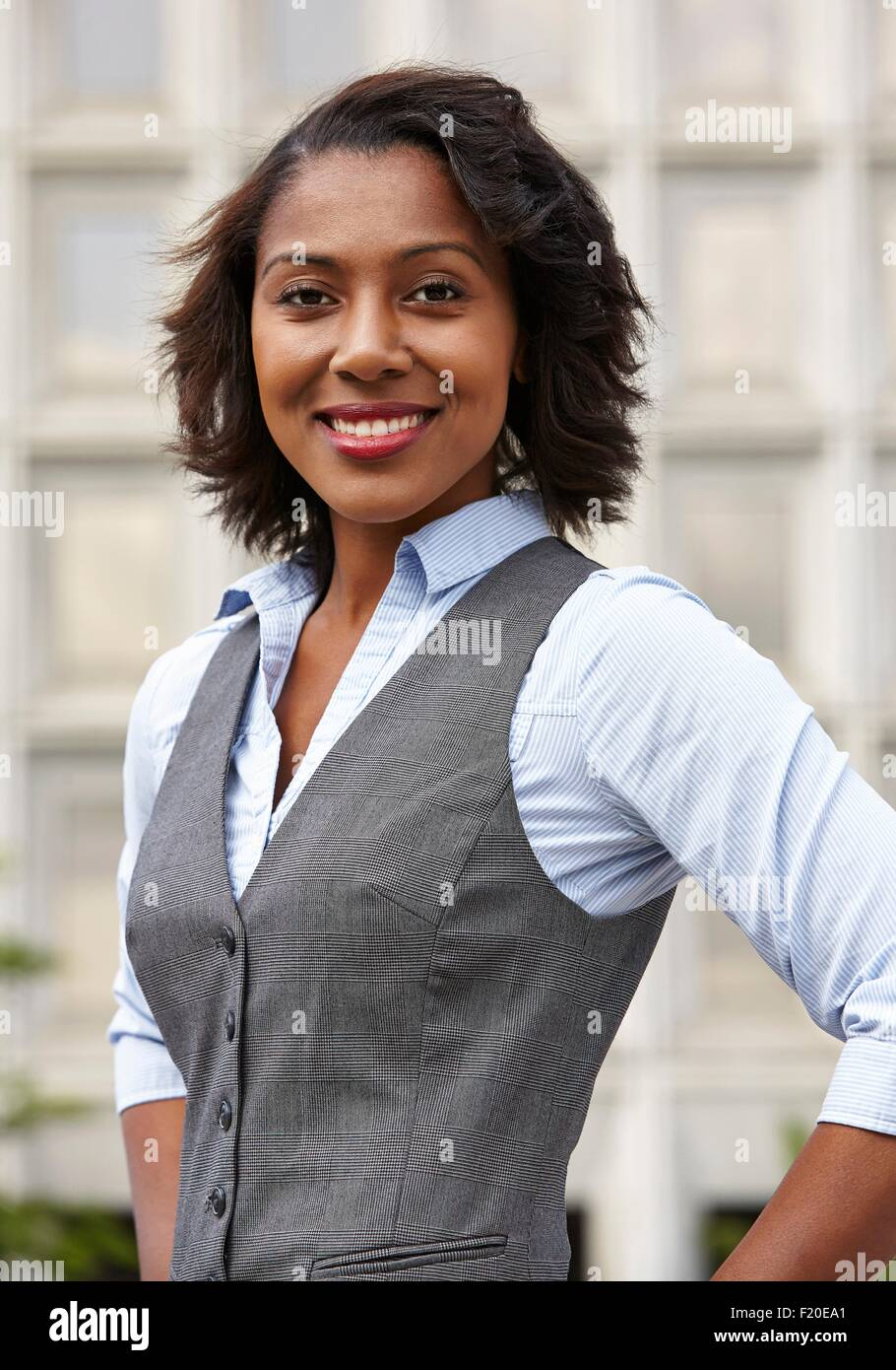 Portrait of young business woman, wearing waistcoat, hands on hips, looking at camera, smiling - Stock Image