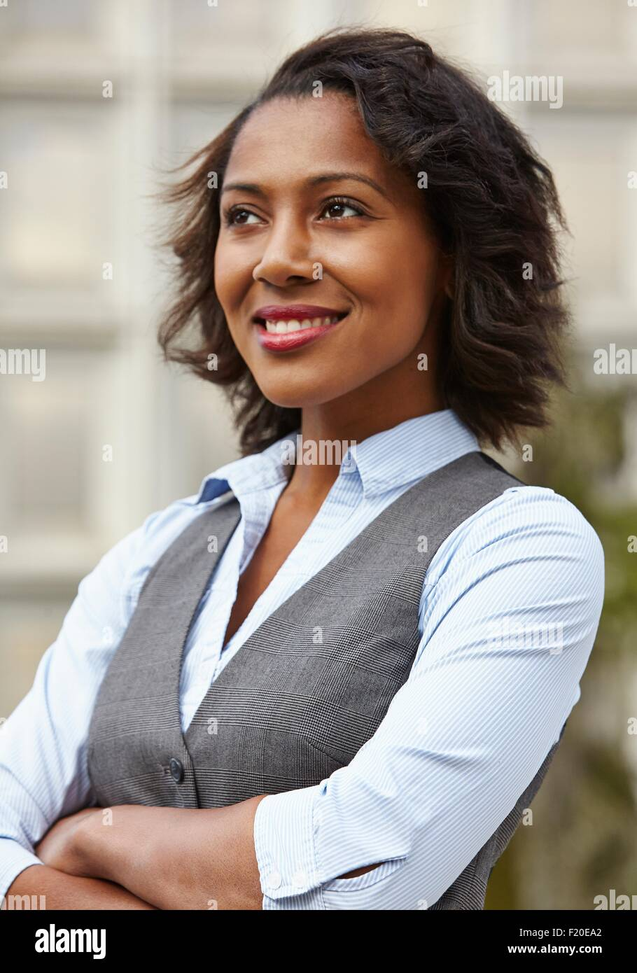Portrait of young business woman, wearing waistcoat, looking away, arms folded, smiling - Stock Image