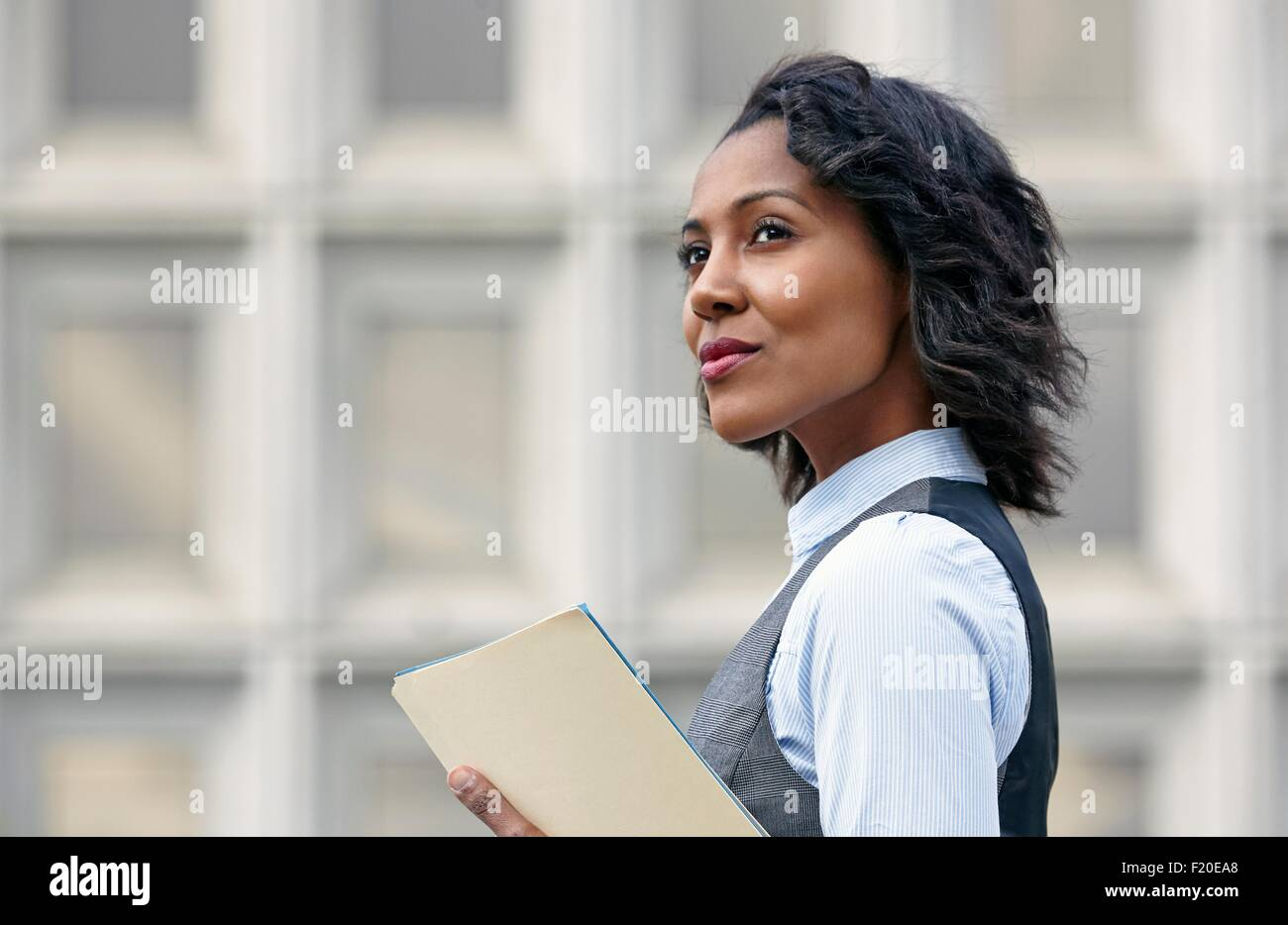 Portrait of young business woman holding paper work, looking away, side view - Stock Image