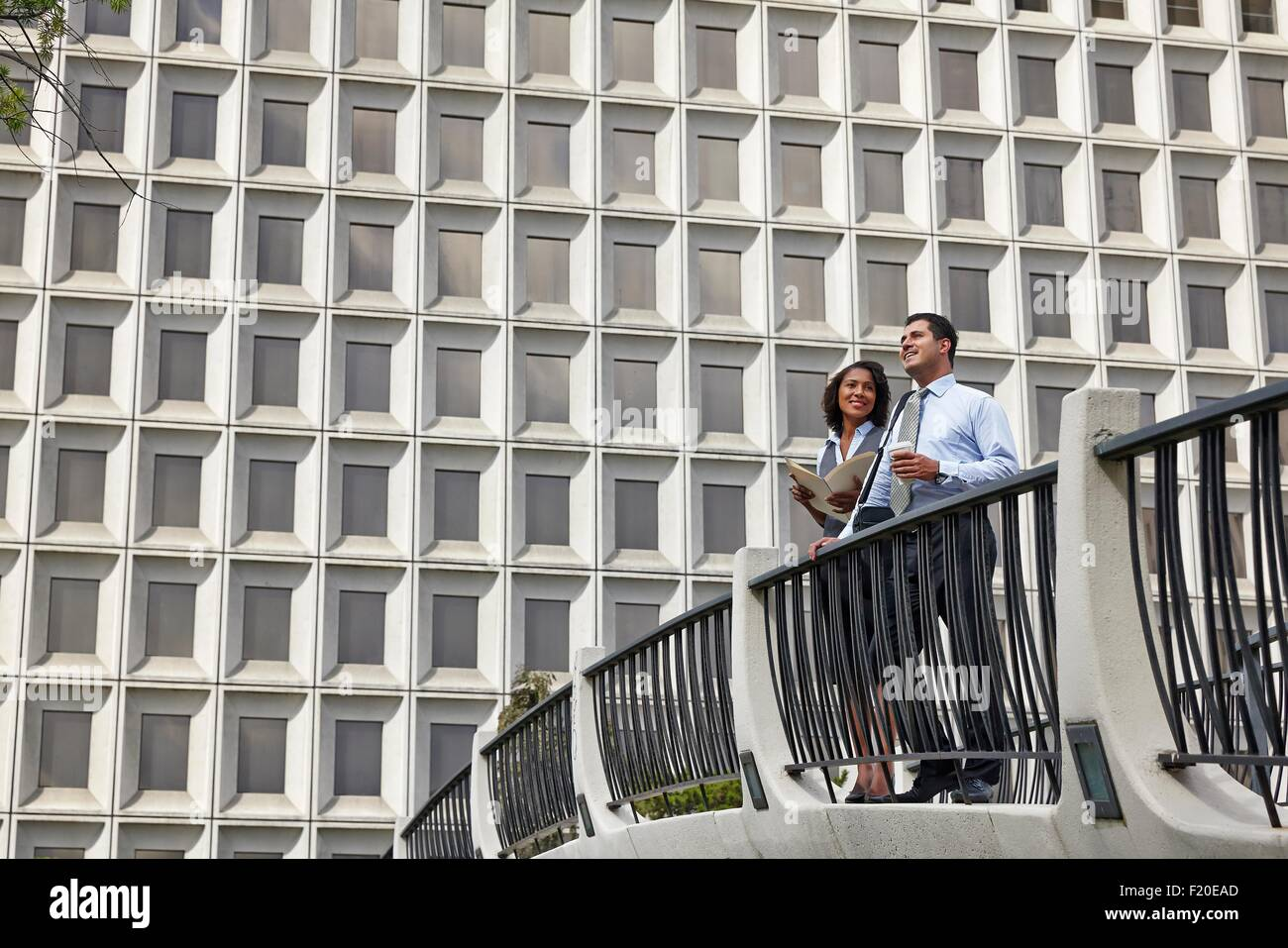 Business people standing behind railings in front of built structure - Stock Image