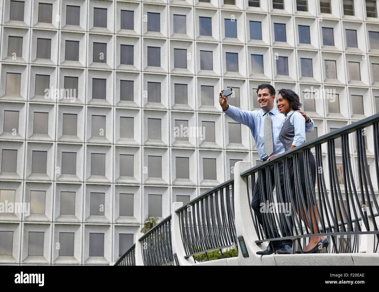 Business people standing behind railings in front of built structure, using smartphone to take selfie - Stock Image