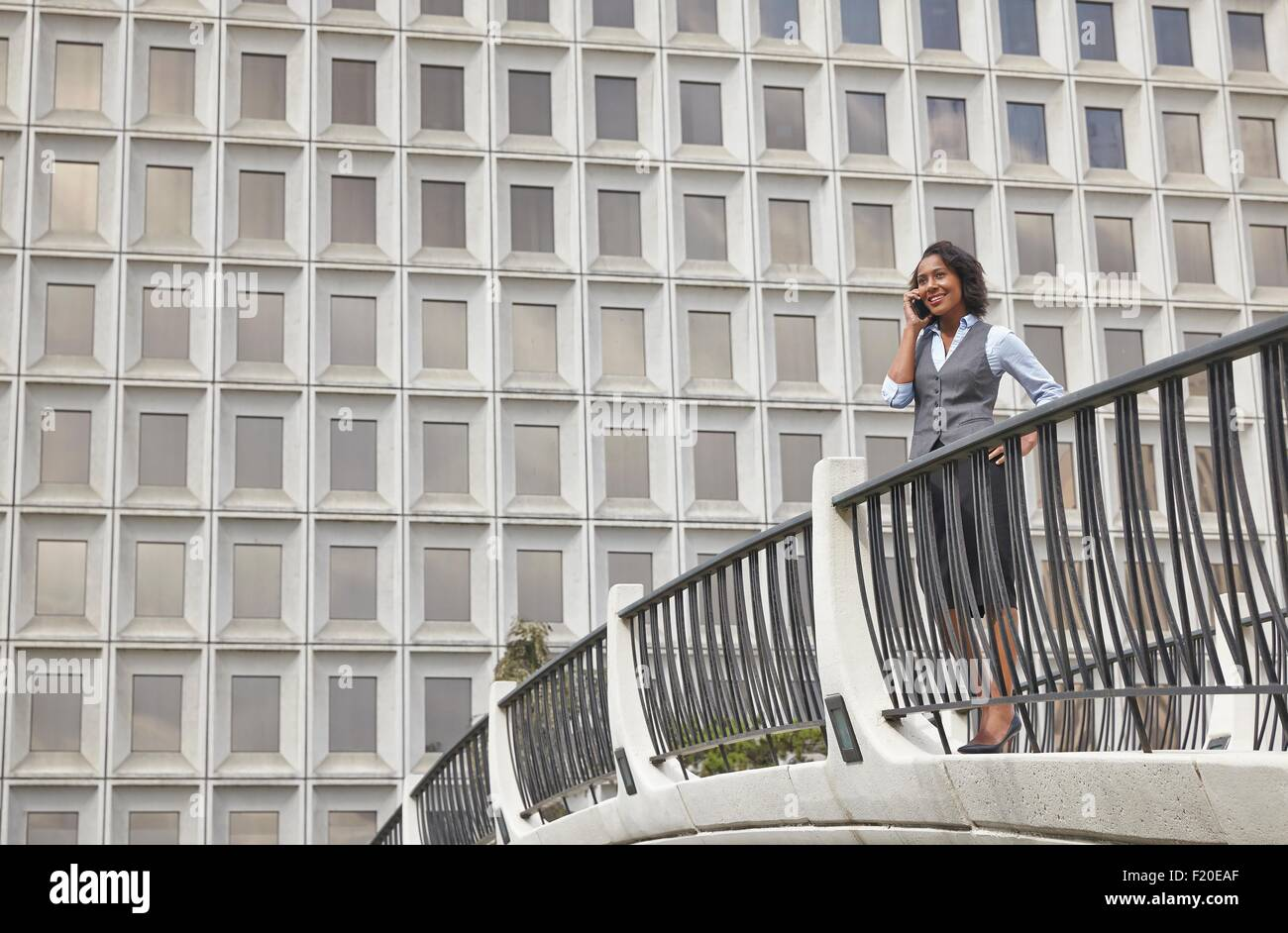 Business woman standing behind railings in front of built structure, using smartphone to make call - Stock Image