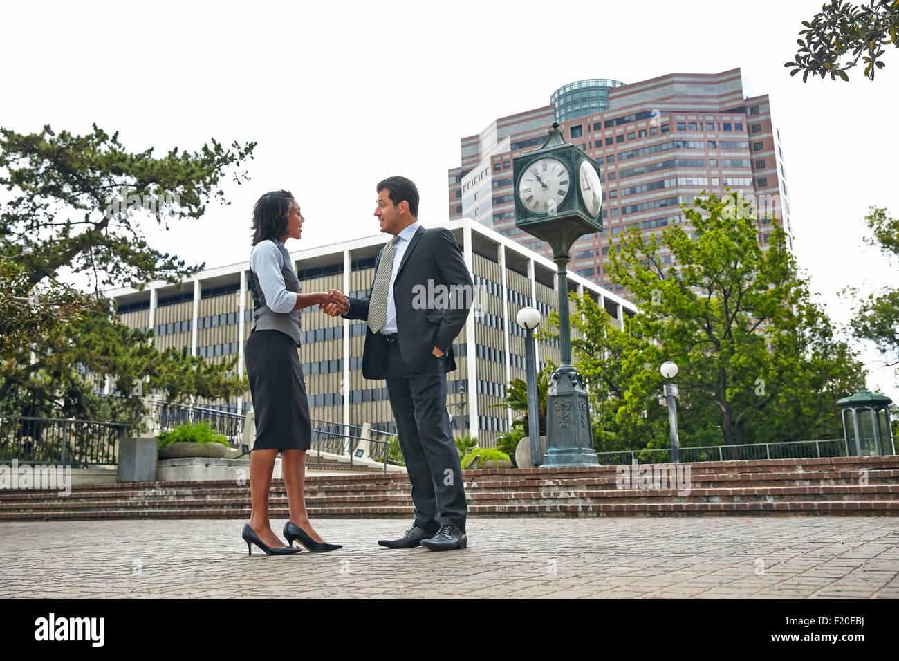 Full length side view of business people shaking hands - Stock Image