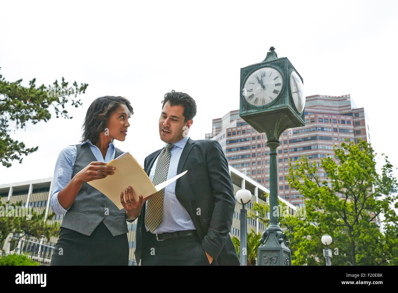 Front view of business people standing next to clock looking at paperwork, waist up - Stock Image