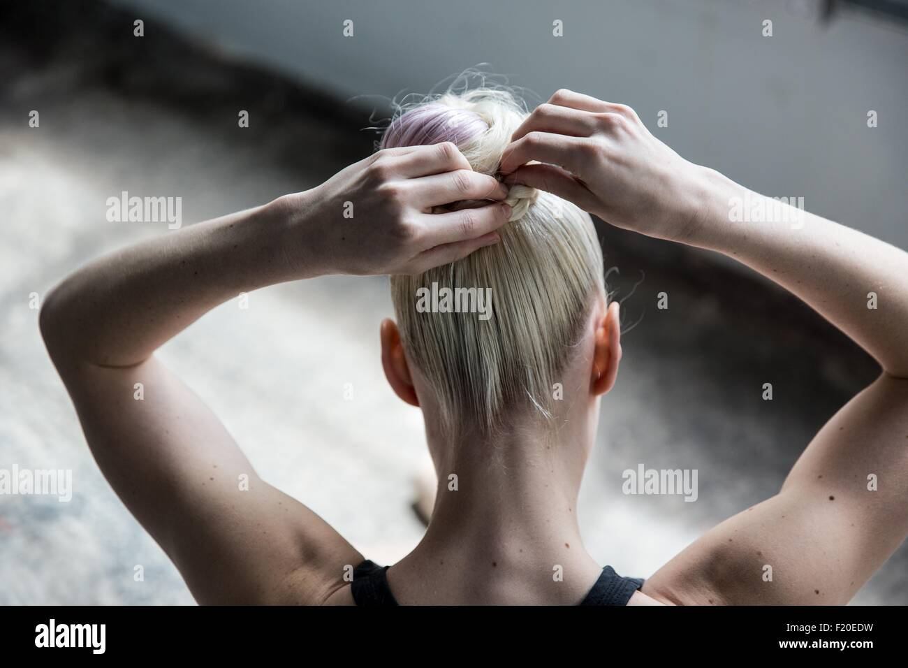 Woman tying up hair in studio Stock Photo