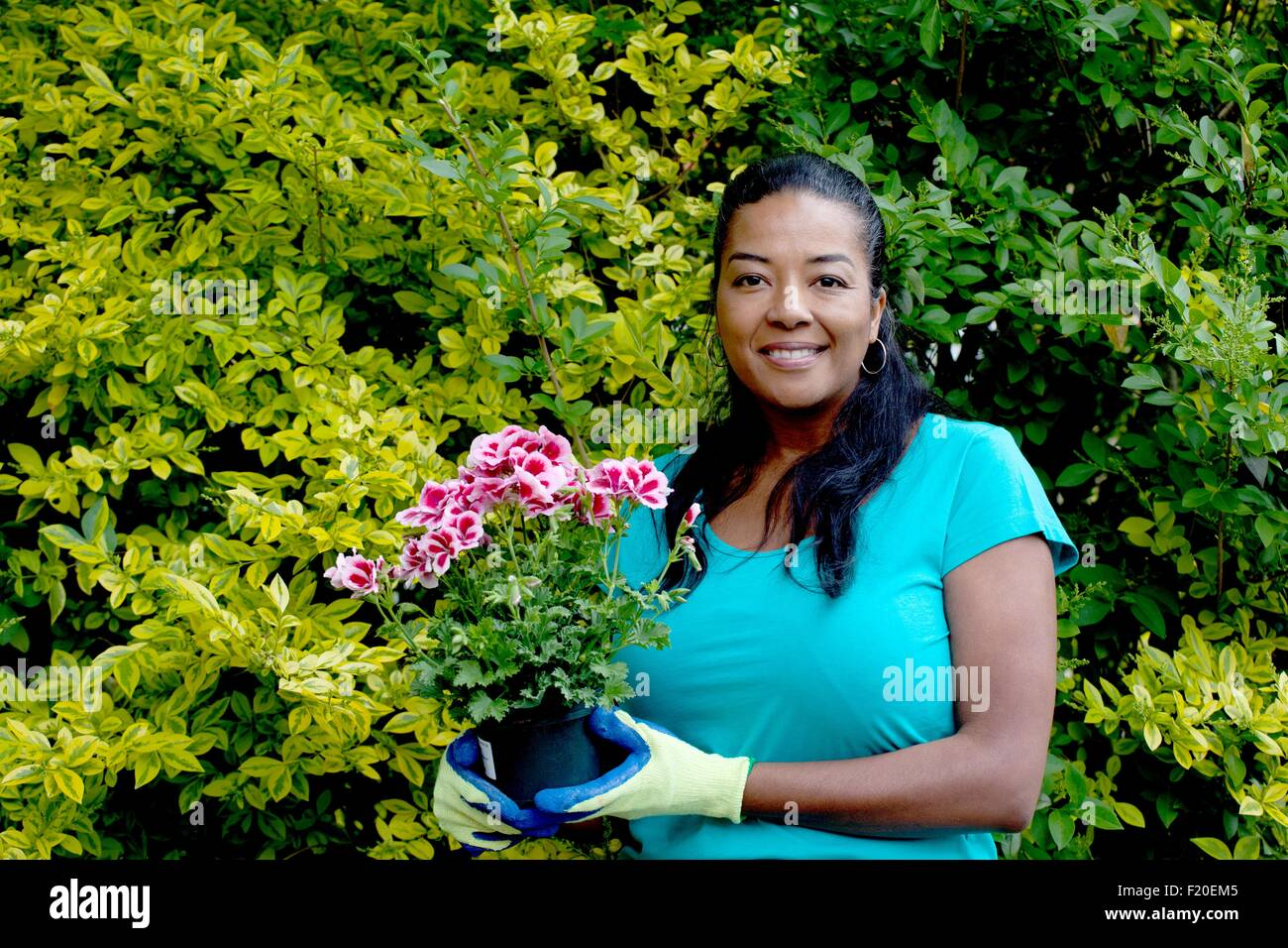 Portrait of mature woman with flowering pot plant in garden - Stock Image