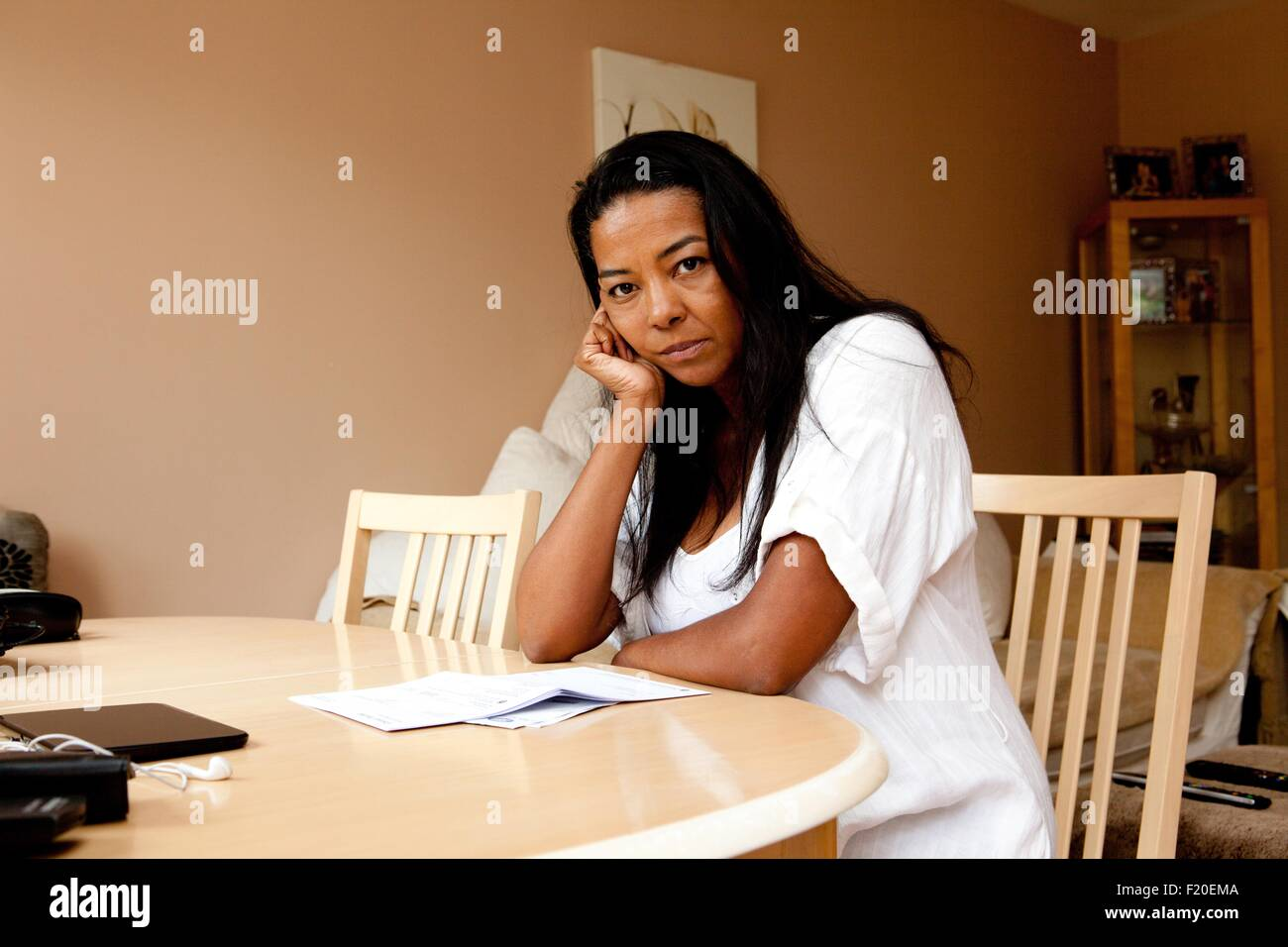 Portrait of fed up mature woman sitting at dining table reading bill - Stock Image
