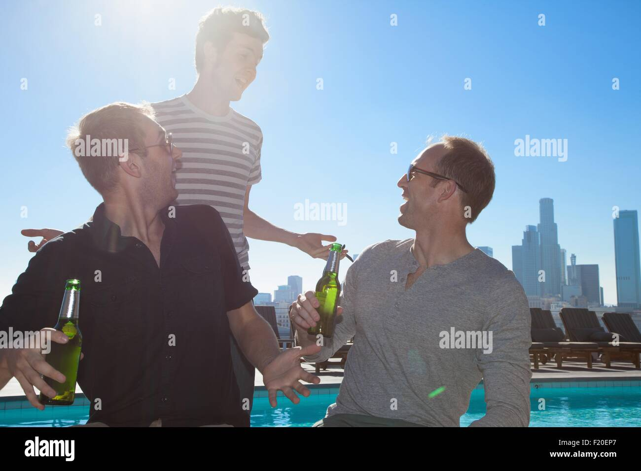 Three adult male friends drinking beers at rooftop bar with Los Angeles skyline, USA - Stock Image